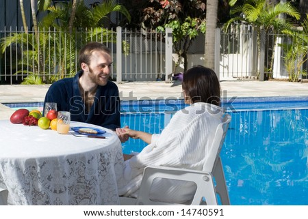 A young and attractive couple, sit down at a fruit covered table, and talk and smile to each other while at the poolside. - horizontally framed