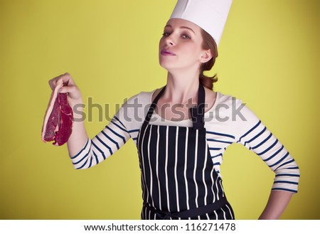 A young and attractive female chef holding a nice piece of steak ready to be cooked to perfection. Nice steak.