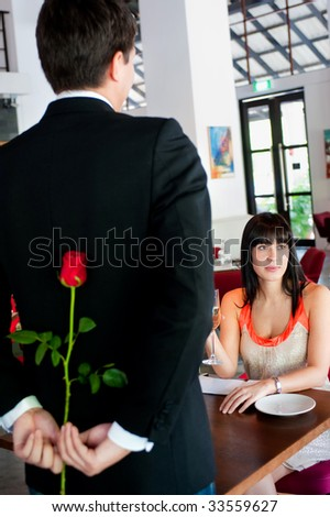 A young and attractive man holding a rose behind his back to surprise his partner in a restaurant