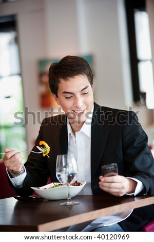 A young and attractive man uses his phone while eating a salad in an indoor restaurant - stock photo