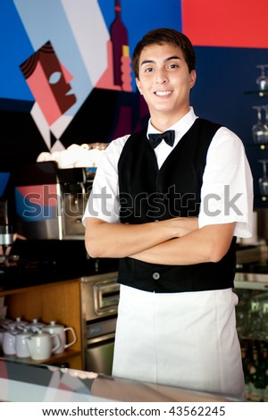 A young and attractive waiter stands behind the bar in an indoor restaurant