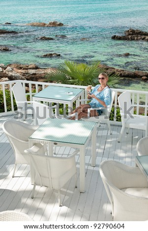 A young and attractive woman having a coffee break in an modern outdoor ocean view restaurant