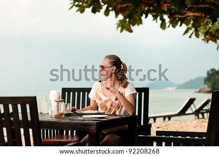 A young and attractive woman having a meal in an outdoor restaurant on a beach