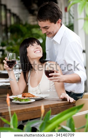 A young and attractive woman is surprised by her partner while dining in an outdoor restaurant
