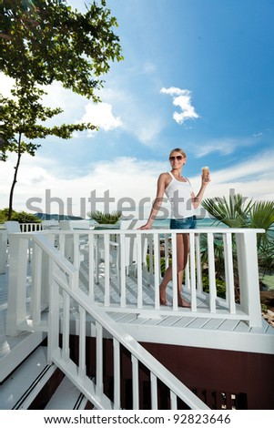 A young and attractive woman stand on a gallery in an modern outdoor ocean view restaurant