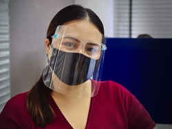 A young and beautiful Asian woman wearing a surgical mask and face shield to protect against Covid-19 while working in an office.
