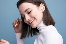 A young and beautiful brunette listens to music on wireless headphones in the studio on a blue background. Close-up portrait.