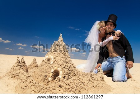 A young and beautiful newly-married couple enjoying on the beach near sandy castle at the sea edge