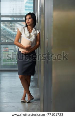 A young and beautiful Thai professional ponders a thought in the hallway of an office building.  20s female Asian Thai model of Chinese descent.