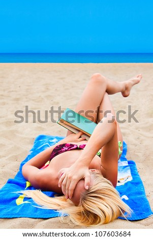 A young and beautiful woman resting on a beach reading a book in hard cover green