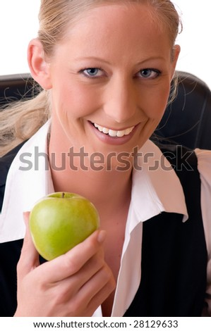 A young and blond woman holds a green apple in her right hand and smiles.