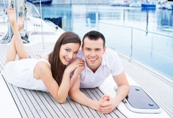 A young and happy Caucasian couple relaxing together on a boat trip.