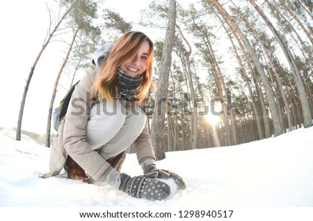 A young and joyful Caucasian girl in a brown coat sculpts a snowball in a snow-covered forest in winter. Games with snow in the open air. Fisheye Photo