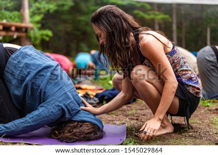 A young and mindful caucasian woman is seen placing her hands on the head of a person worshipping sacred ground during a retreat celebrating enlightenment. #1545029864
