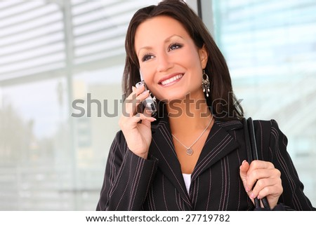 A young and pretty business woman on phone at office