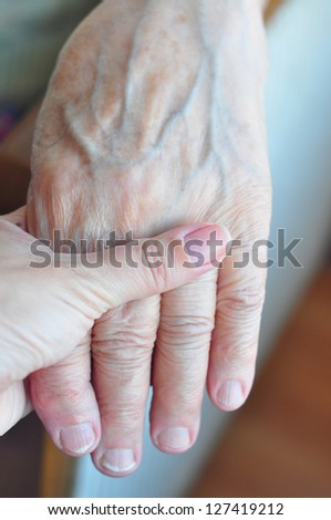 a young and senior hands holding each other