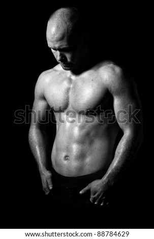 a young and very fit male model posing his muscles