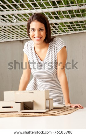 A young architect looking at the camera smiling with a rough model house