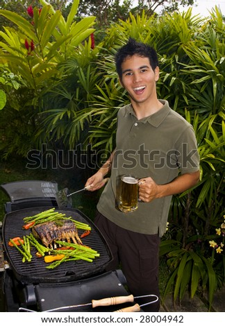 A young Asian American man grilling rack of lamb on a barbecue in his yard
