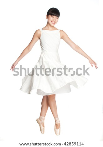 A young asian ballerina does a ballet pose against white background - stock photo
