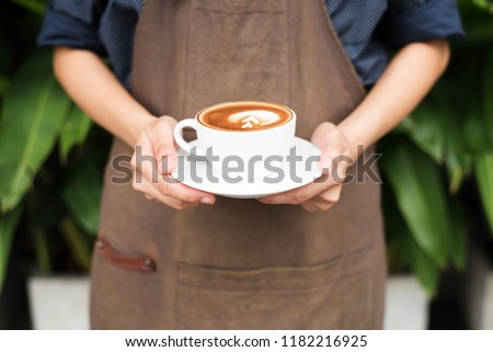 a young asian barista holding a latte art in front of customer, a young a barista serving a latte art.