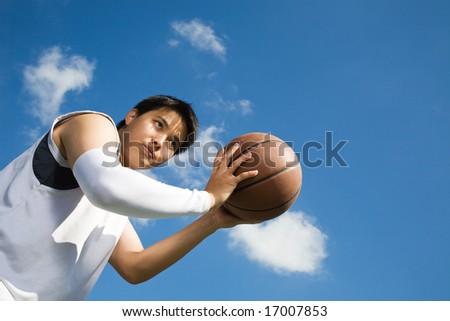 A young asian basketball player shooting a basketball