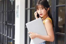 A young asian business woman, beautiful female model is calling with her smartphone while holding a laptop at the office with yellow cloth looking pretty