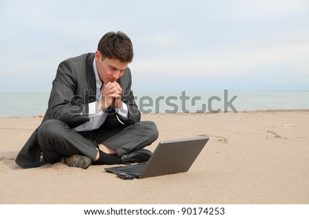 A young Asian businessman sitting on the beach in front of the laptop. He thought about business.