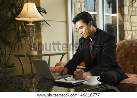 A young Asian businessman typing on a laptop computer whiles taking notes on a notebook. Horizontal shot.
