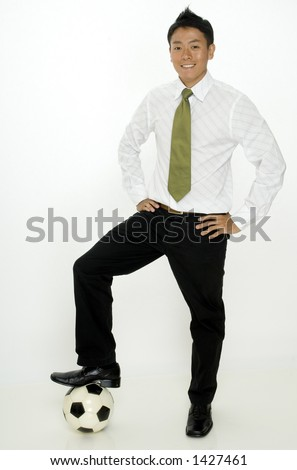 A young asian businessman with his foot on a football (soccer ball)