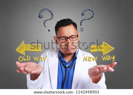A Young Asian confused doctor trying to decide which side to choose, Old way or new way #1142498903