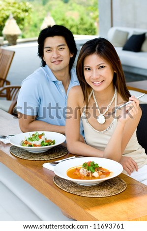 A young Asian couple enjoying lunch outdoors
