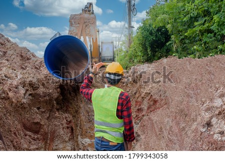 A young Asian engineer is inspecting a large sewer that is buried underground at a construction site. The excavator is empty the water pipe. Foto stock ©