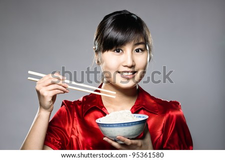 A young Asian girl eating rice with bowl and chopsticks