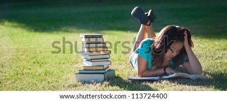 A young Asian girl studying outside in the grass
