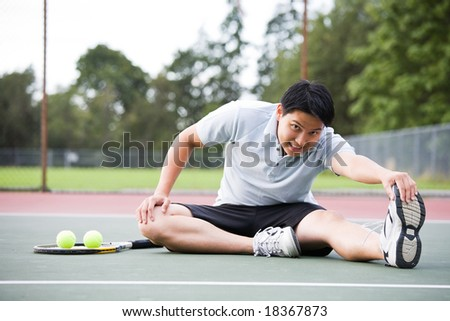 A young Asian male tennis player stretching before playing