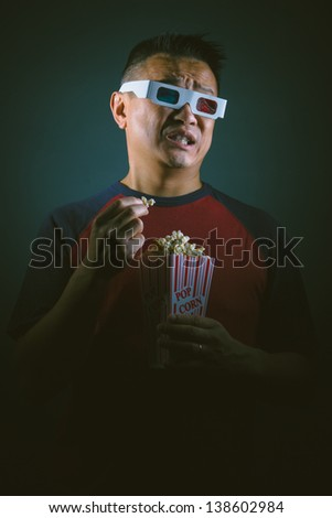 A young Asian man  in an entertainment setting with 3D glasses watching a horror movie