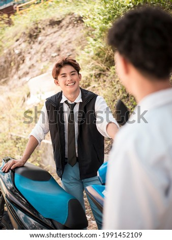 A young asian man listens avidly to some compliments about his motorbike. Сток-фото ©