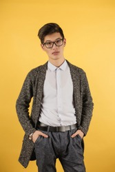 a young Asian man of madness with a fashionable haircut in a white shirt, a gray cardigan and glasses on a yellow background