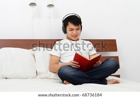 A young Asian man reading a book on a bed