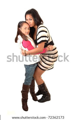 A young Asian mother hugging her young daughter, she in a dress and the daughter in jeans and boots
