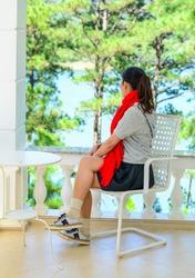 A young Asian woman sitting at luxury villa in Dalat, Vietnam.