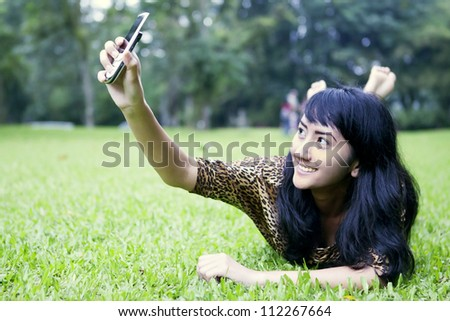 A young asian woman taking a self portrait by using mobile phone in the garden