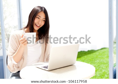 a young asian woman using laptop compute in cafe
