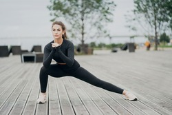 a young athlete does a leg stretching squat exercise. sporting a black suit. look away