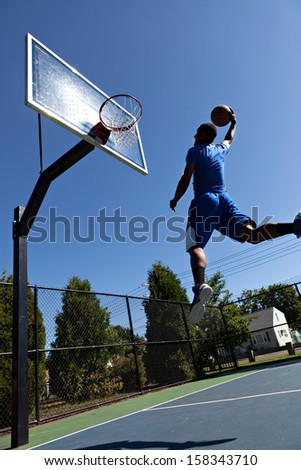 A young athlete flying through the air to dunk the ball into the basket.