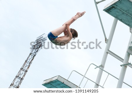 a young athlete performs 1/2 somersault platform 5m in the center of the city in an outdoor pool against the backdrop of an urban view #1391149205