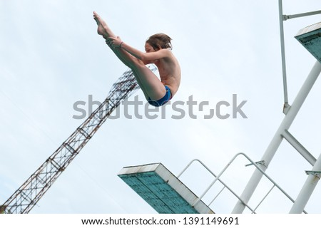 a young athlete performs 1/2 somersault platform 5m in the center of the city in an outdoor pool against the backdrop of an urban view #1391149691
