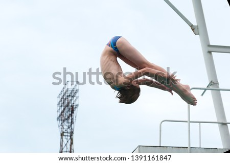 a young athlete performs 1/2 somersault platform 5m in the center of the city in an outdoor pool against the backdrop of an urban view #1391161847