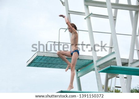 a young athlete start performs 1/2 somersault platform 5m in the center of the city in an outdoor pool against the backdrop of an urban view #1391150372